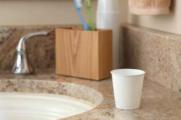 Small white bathroom cup sitting on bathroom counter.