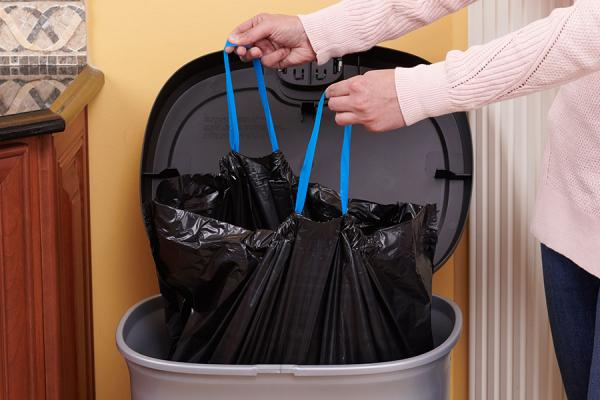Person closing a strong drawstring large bag in a trash can.