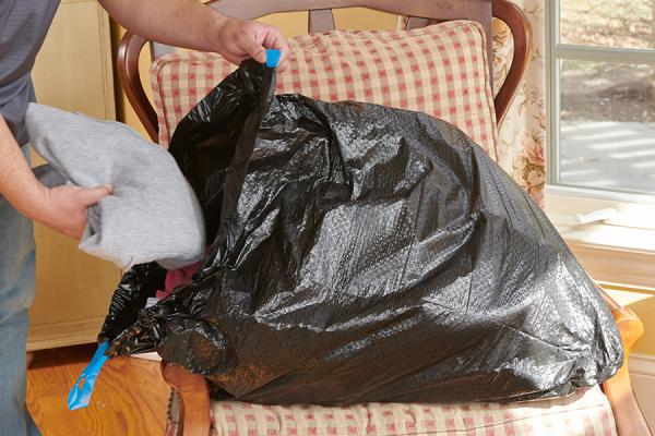 Person putting clothing in an ultra strong large trash bag to donate.
