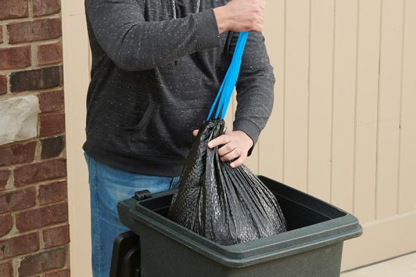 Person pulling the drawstring on an ultra strong large trash bag while placing it in a large trash can.